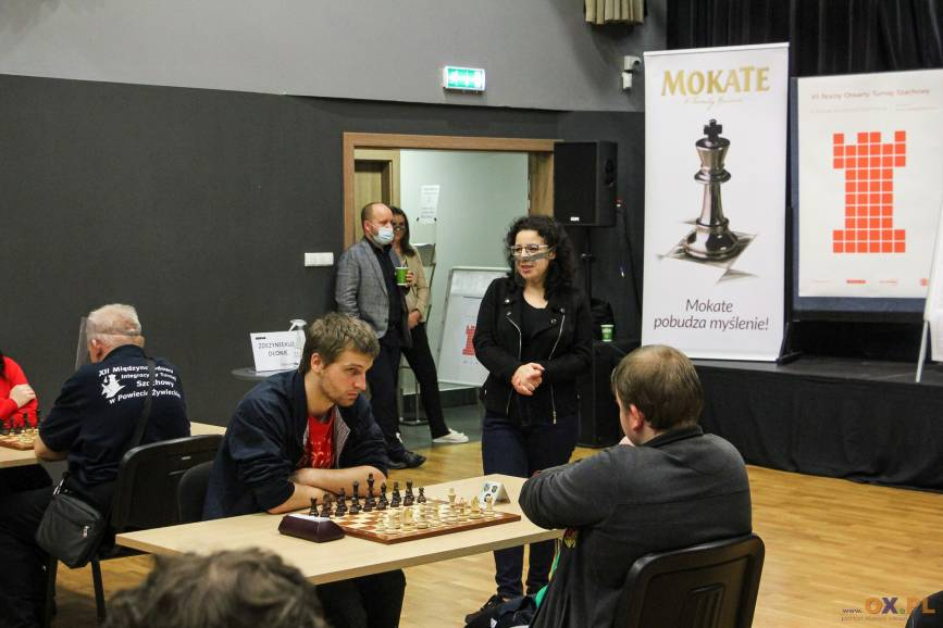 Dwoje mężczyzn grających turniej gry w szachy w tle przemawiająca kobieta