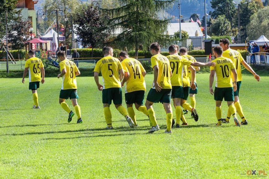 Piłkarze biegnący przed siebie ubrani w żółte koszulk