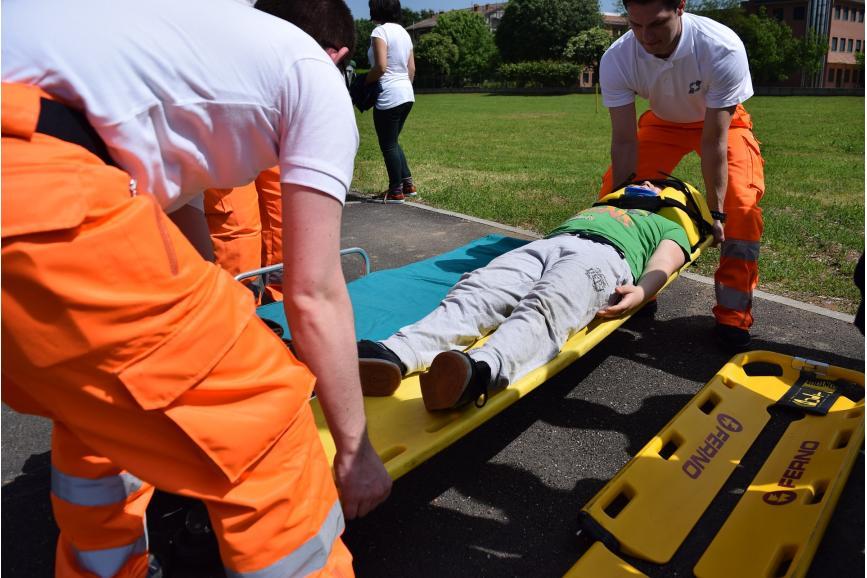 Osoba poszkodowana na noszach , niesiona przez dwóch ratowników
