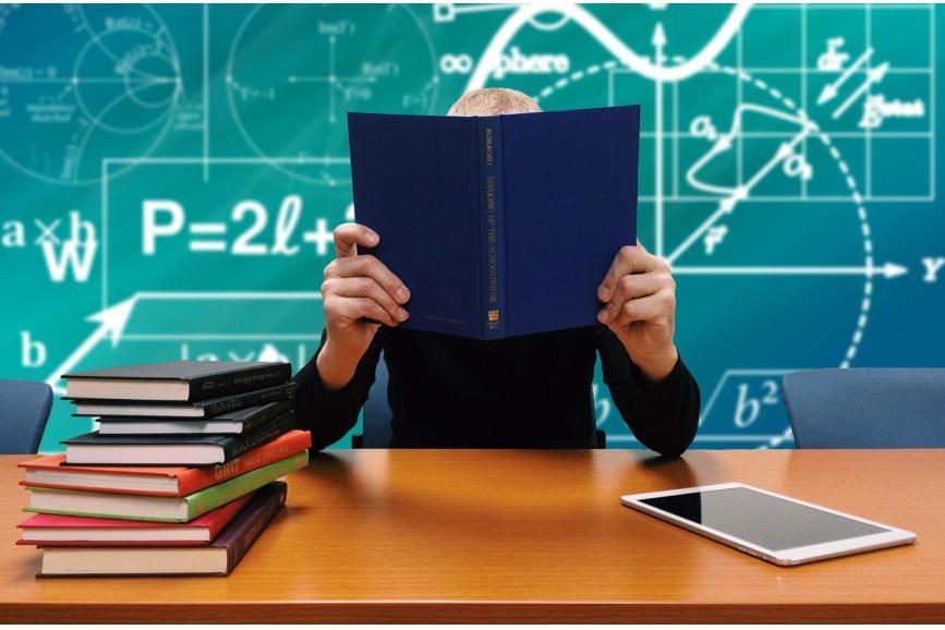 Nauczyciel przy biurku trzymający niebieską książkę