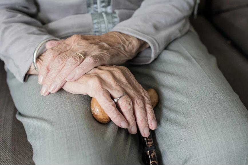 Starszy mężczyzna siedzi z założonymi rękoma i trzyma laskę