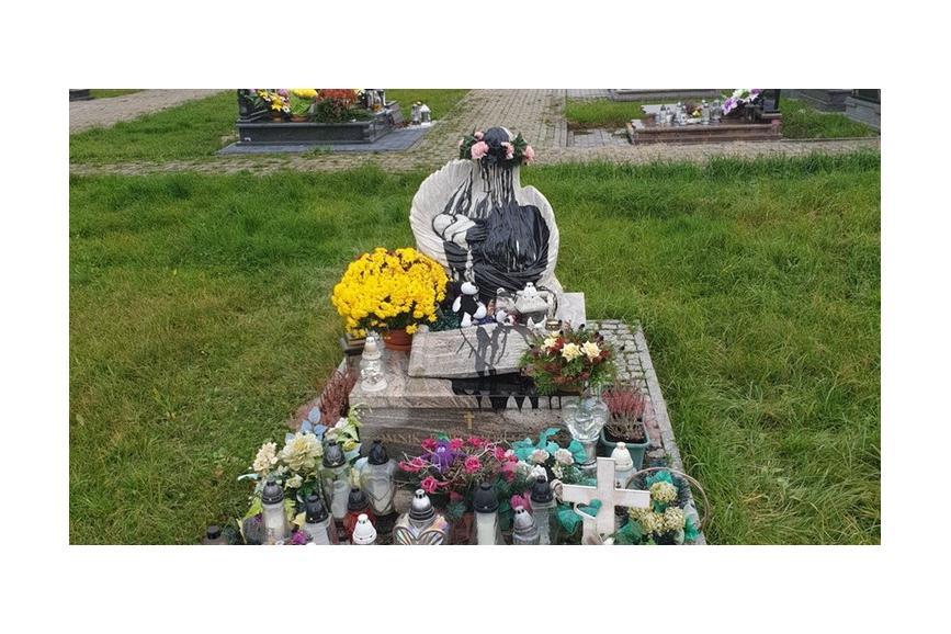 zdjęcie przedstawia pomnik anioła trzymającego w rękach niemowlaka, pomnik jest oblany czarną farbą. Przed pomnikiem płoną znicze oraz położone są maskotki. fot. G.Sikorski